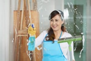 Smiling Vietnamese woman cleaning glass with window washer